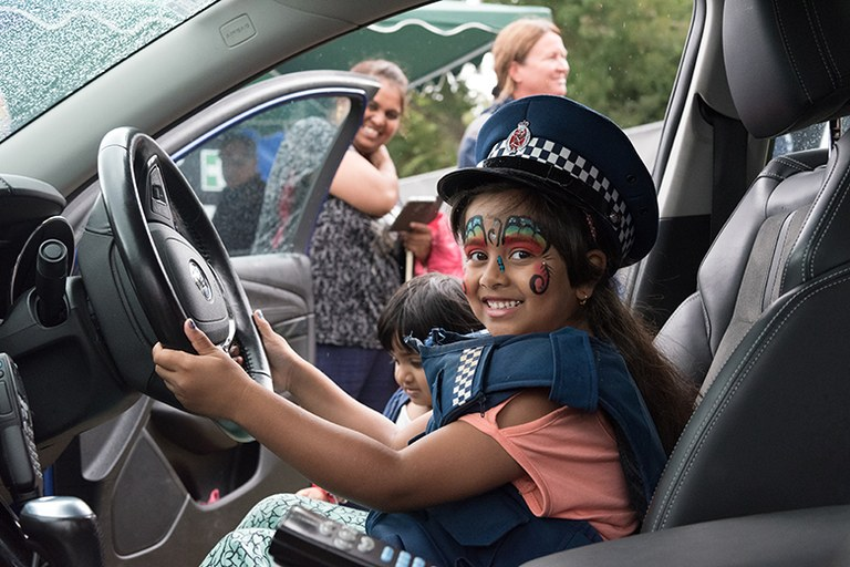 Young girl inside of a police car enjoying pretending to drive it.